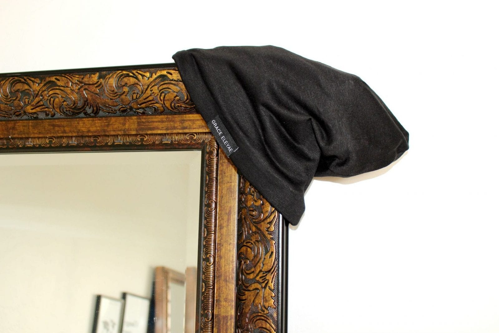 This is a close up of the Grace Eleyae Satin Lined Cap hanging on a mirror.