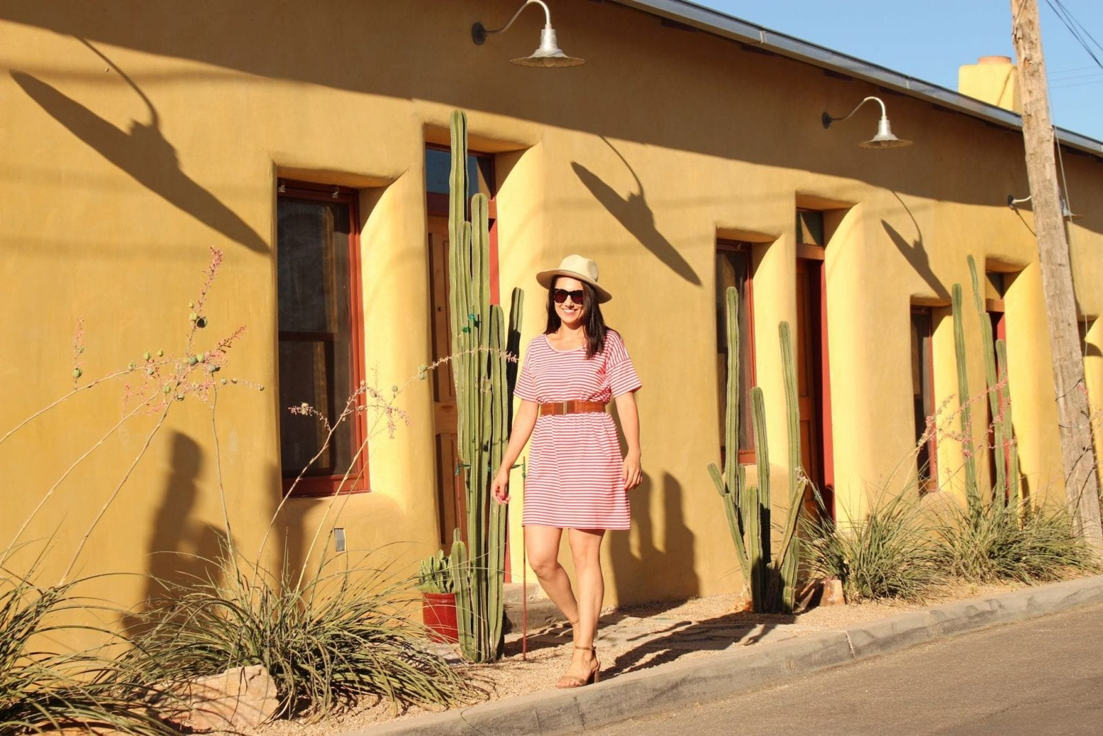 This is a scenic shot with a yellow house background, while I'm wearing a red striped Everlane dress.