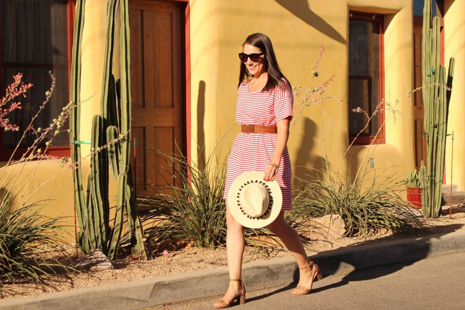 This is a close up of me walking down the street in a red striped dress from Everlane.