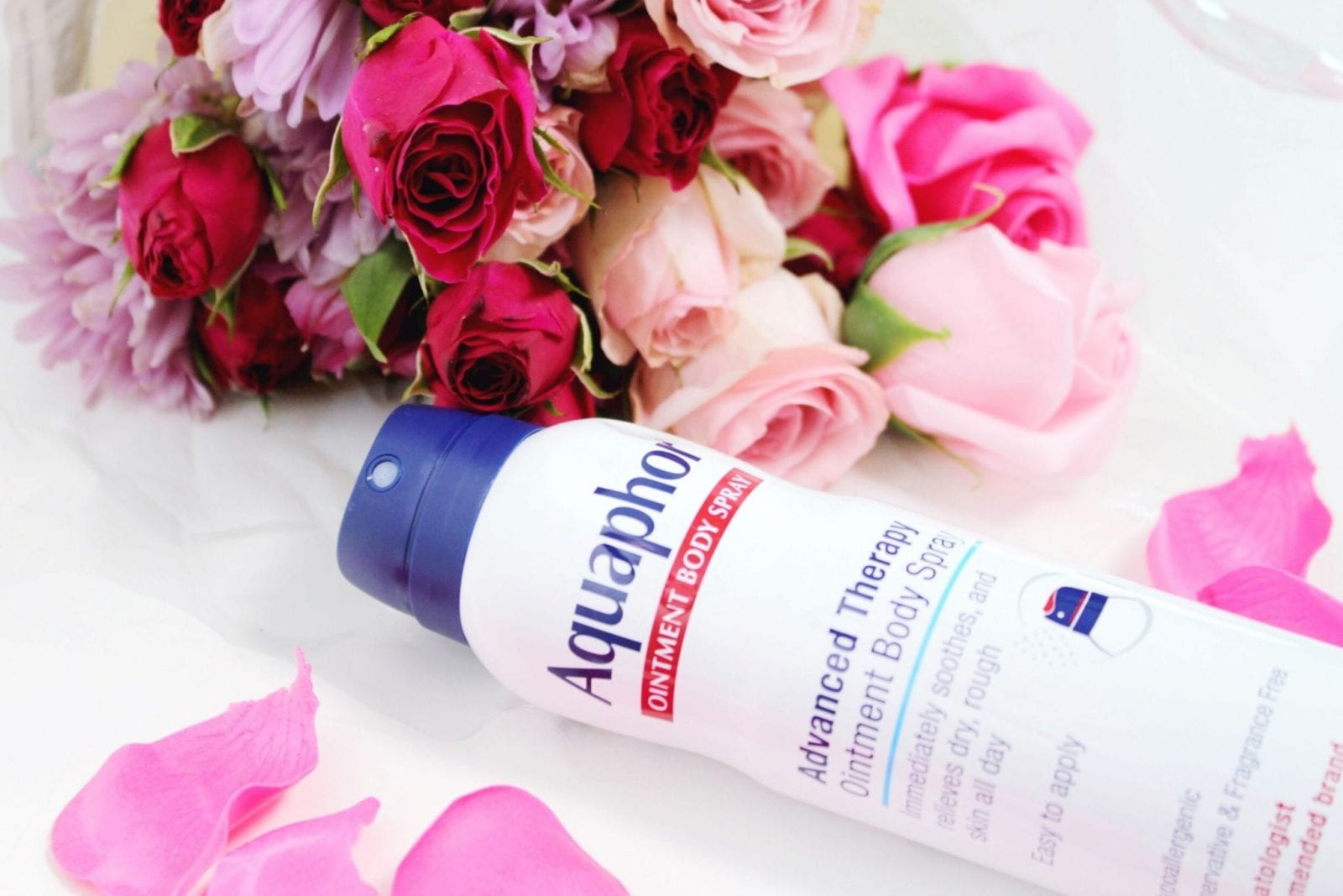 AquaphorⓇ Ointment Body Spray is in the center on its side, of the photo surrounded by flowers.