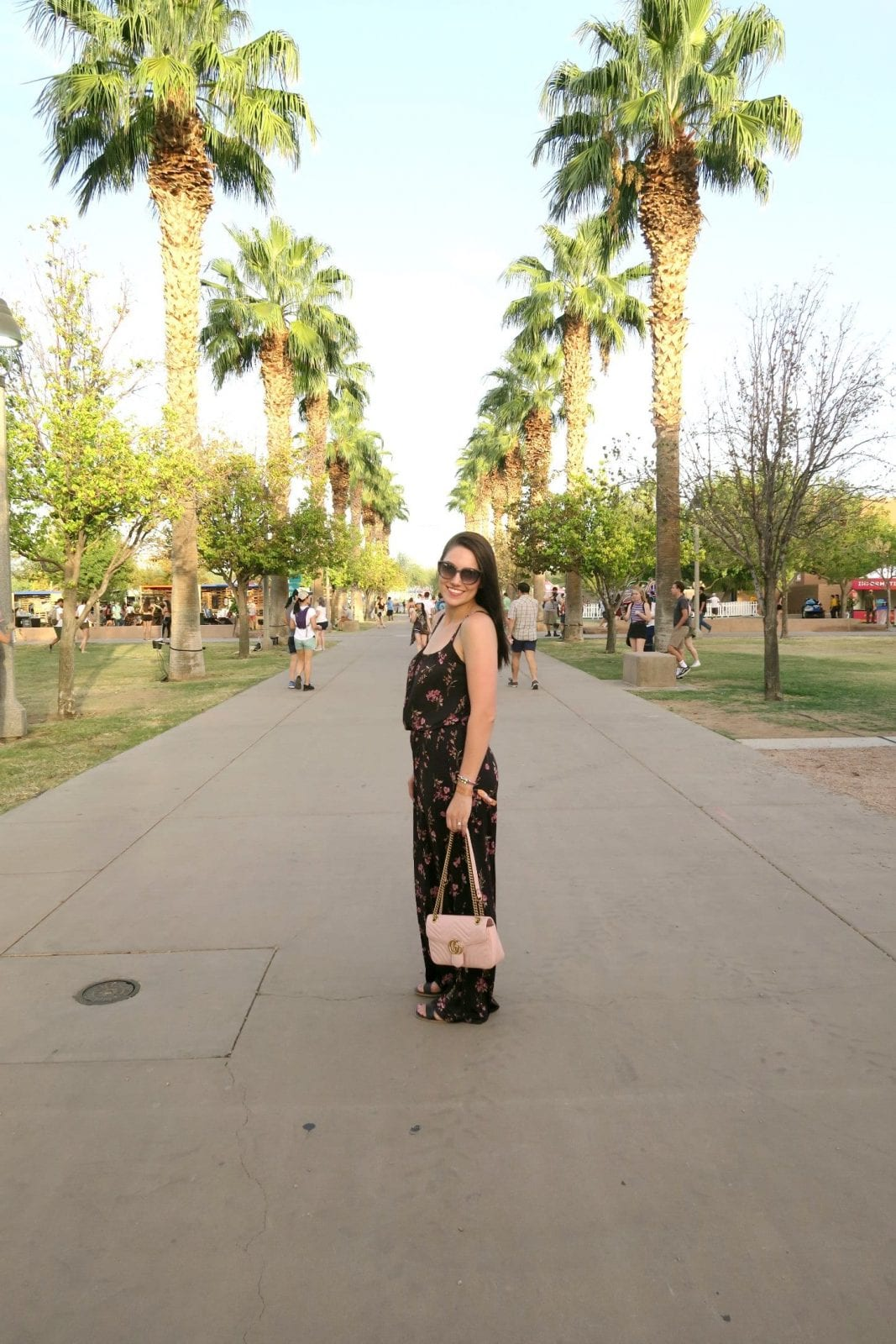 This is a scenic shot of me standing in front of rows of palm trees in a blue floral jumpsuit at the Lost Lake Festival.