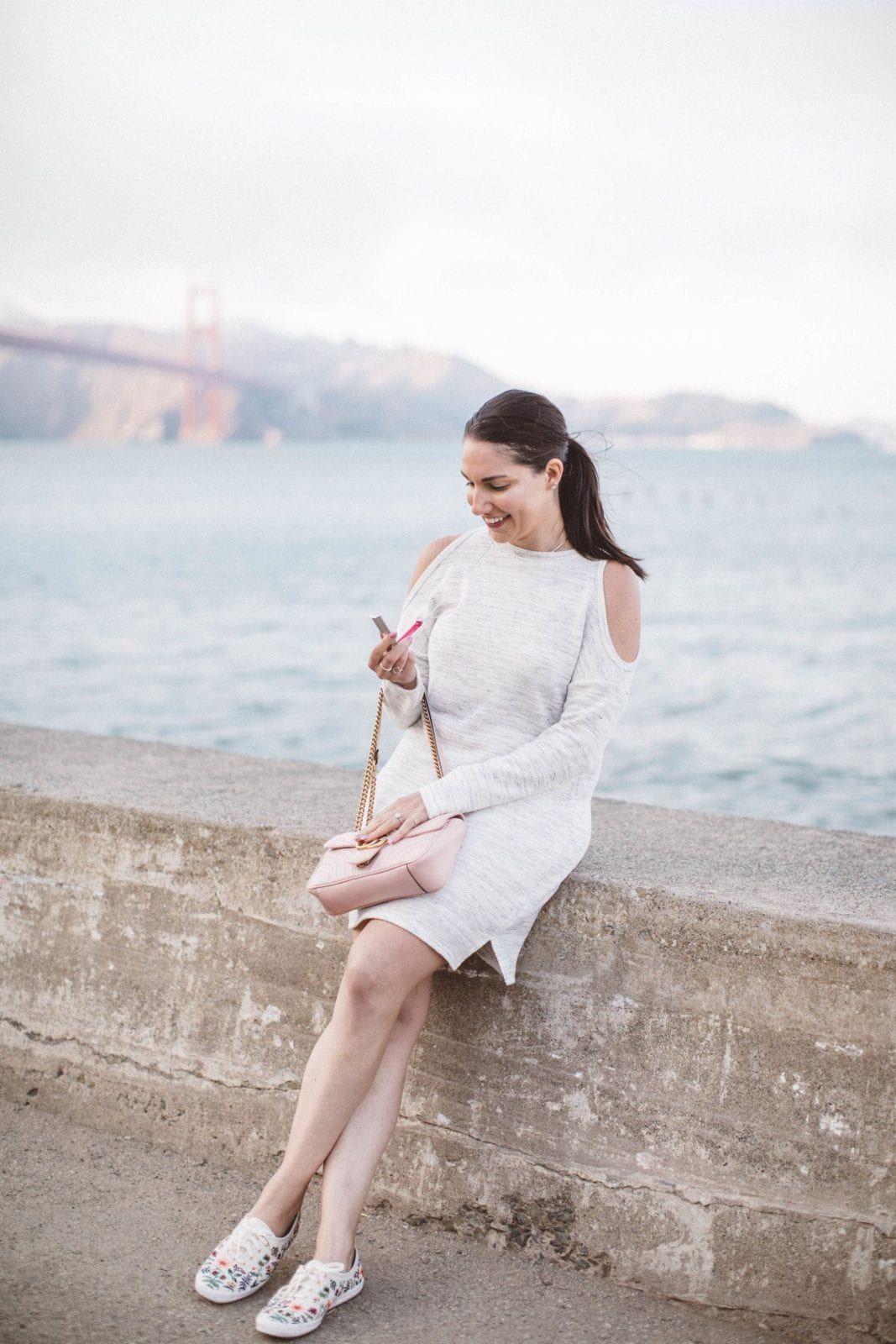 This is a shot of me sitting in front of the Golden Gate Bridge holding my Cosmetic Hideaways necklace.