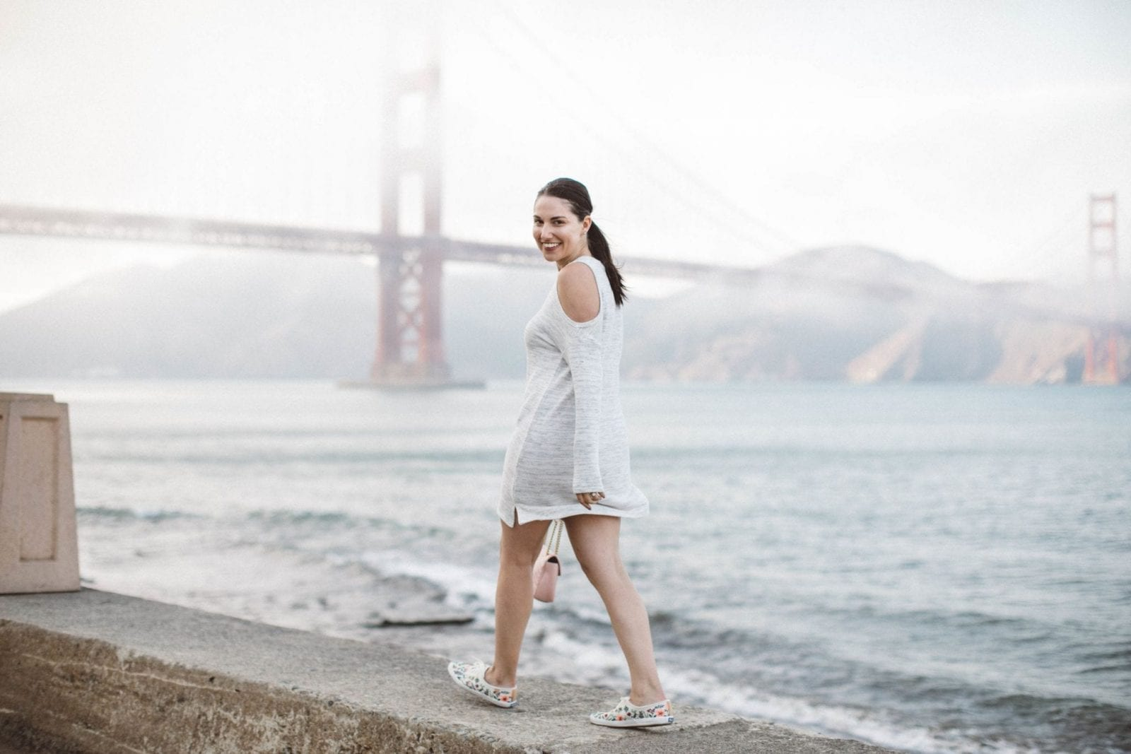 This is a full body shot of my cut-out white sweater dress, featuring Keds and a Gucci bag in front of the Golden Gate Bridge.