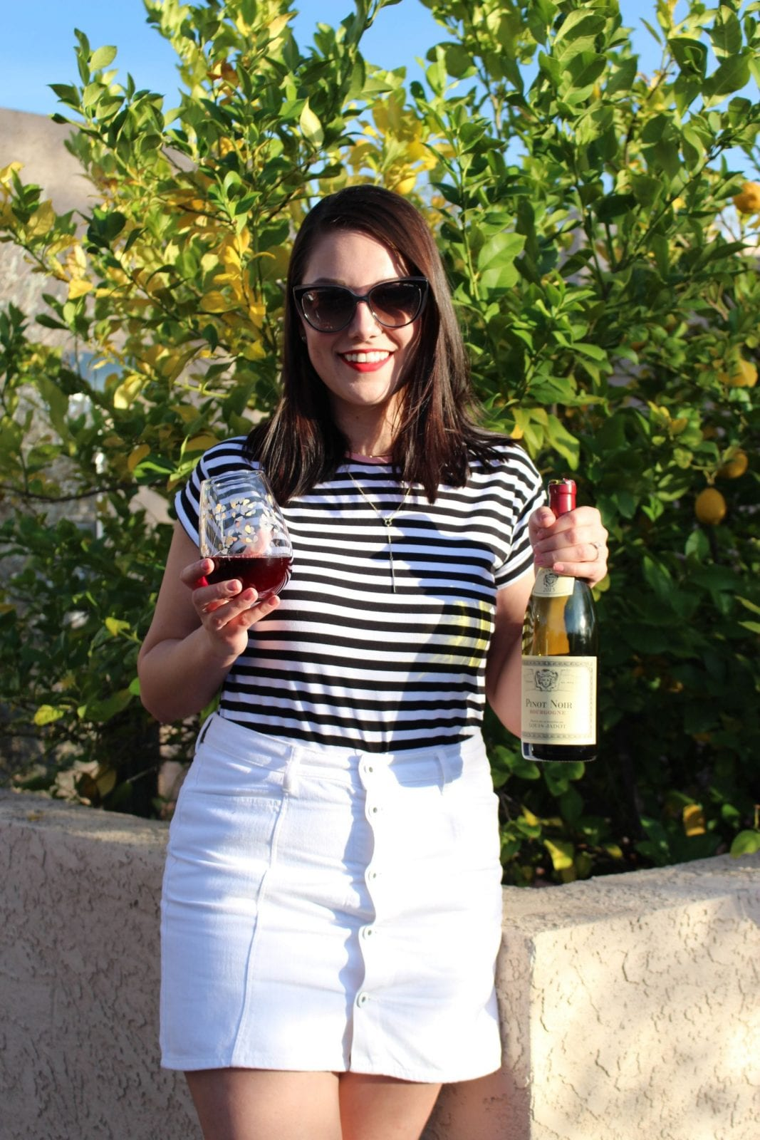 This is a close up shot of me holding a bottle of Louis Jadot, and a glass of wine in my other hand.
