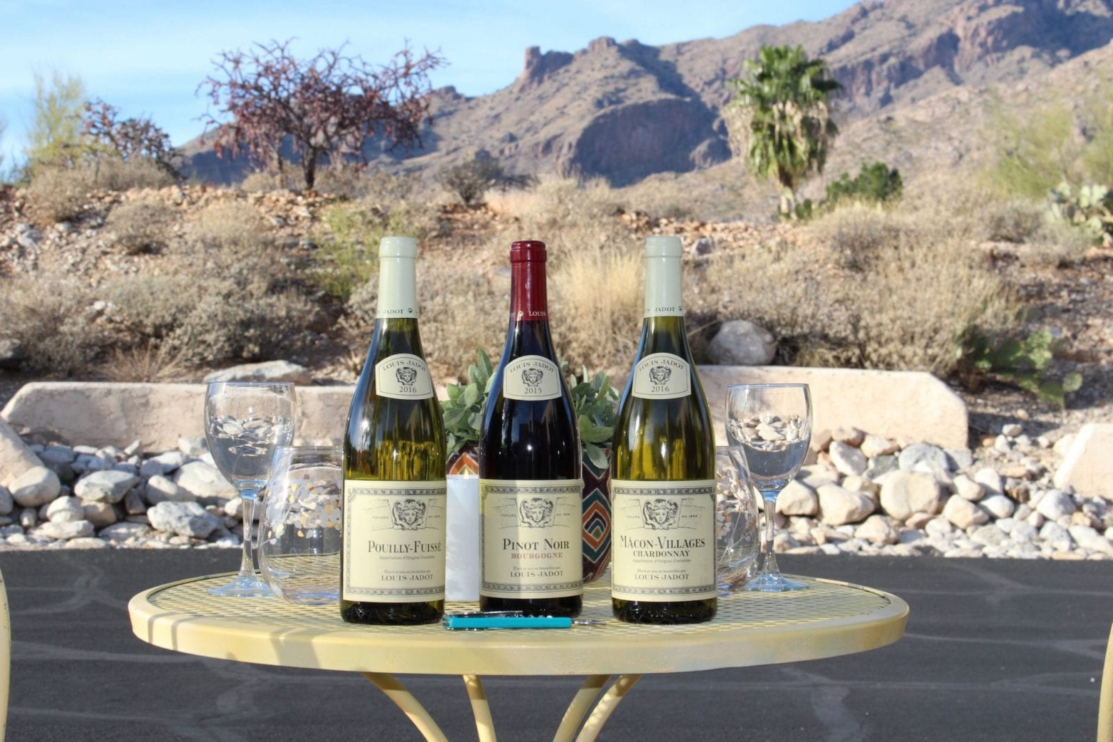 This is a close up of the Louis Jadot wines on a gorgeous yellow picnic table, with the Sonoran Desert scenery in the background.
