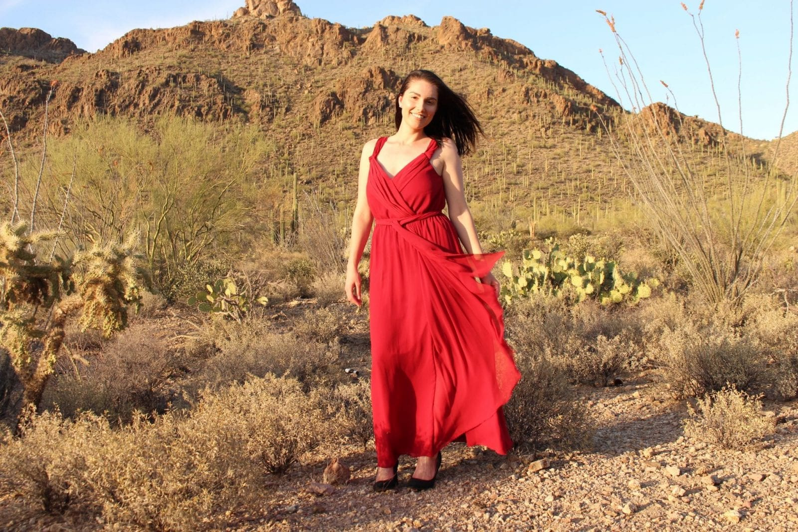 This is an image of Adaleta Avdic wearing a gorgeous long slitted red bridesmaid dress in the desert.