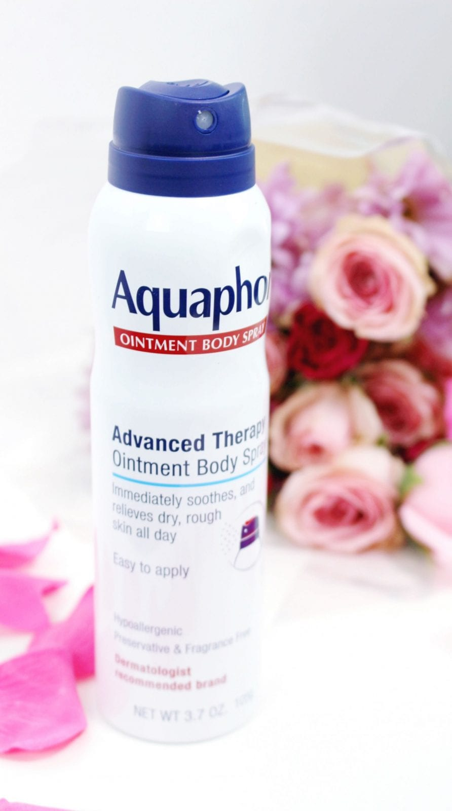 This is a standing close up of the AquaphorⓇ Ointment Body Spray, surrounded by roses.