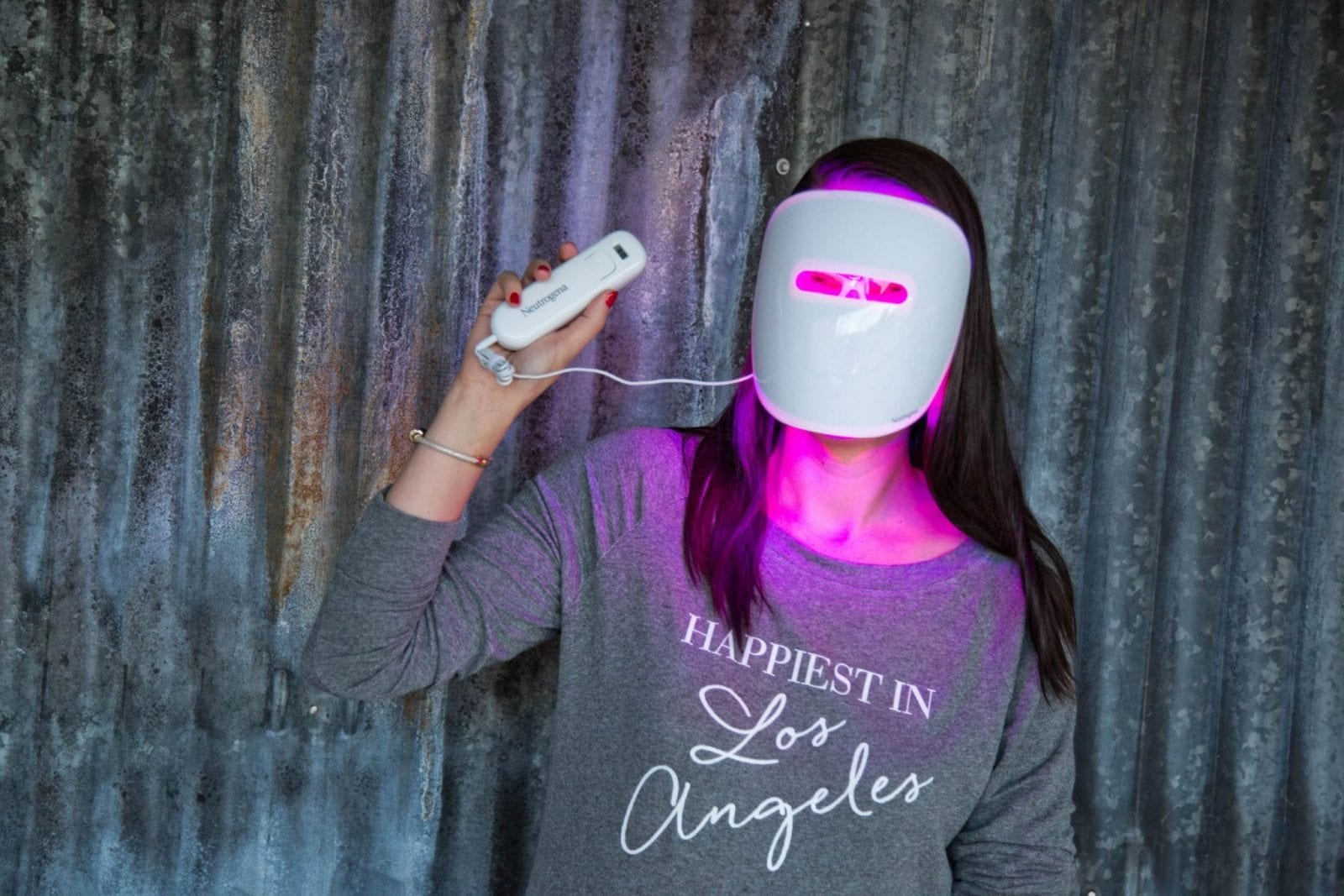 In this photo, I am wearing the Neutrogena Light Therapy Mask with the light turned on so my face is illuminated in purple.