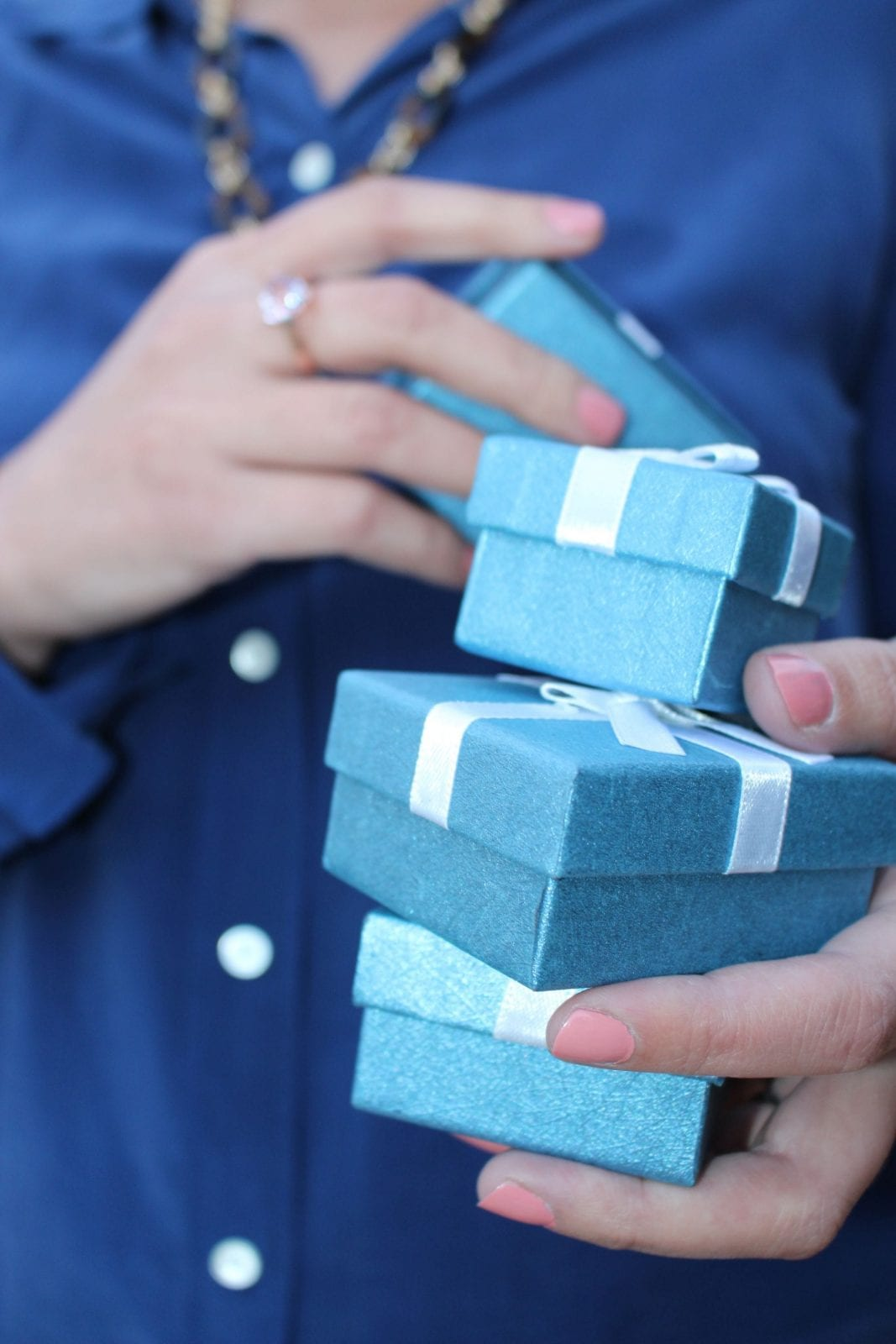 This is a close up of me holding all the Shop LC blue boxes.