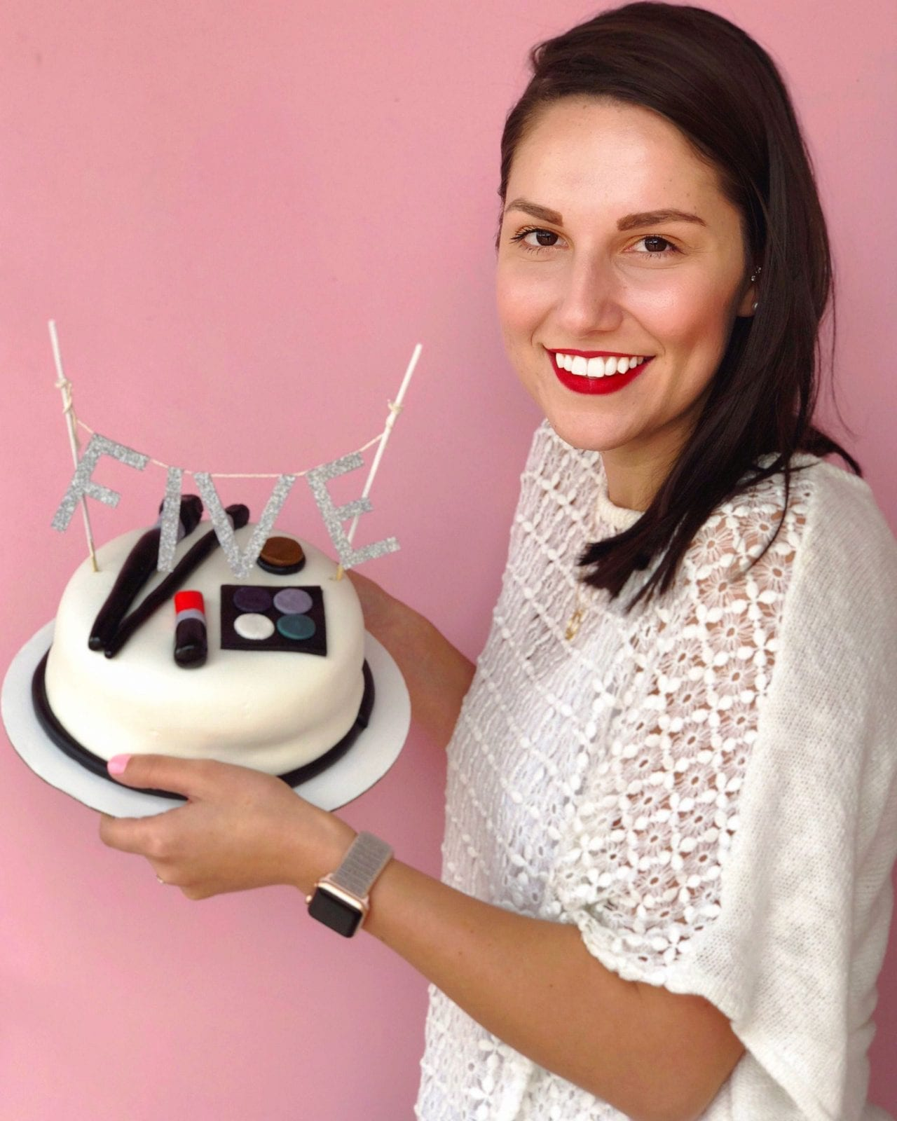 This is a close up of me holding a cake celebrating 5 years of blogging, and my hair in its state after washing my hair with Nexxus for several days.