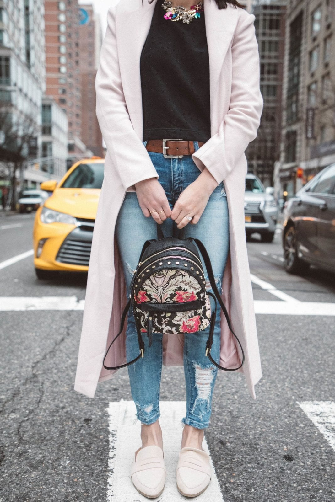 This is a detail shot of me holding my Sam Edelman backpack in the middle of the street in New York City.