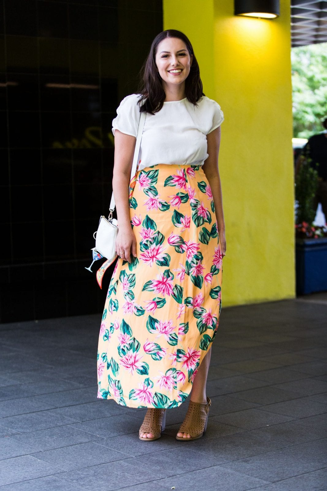 This is a full body shot of me standing outside Hotel Rose in Portland Oregon, with a gorgeous orange floral skirt from Revolve.