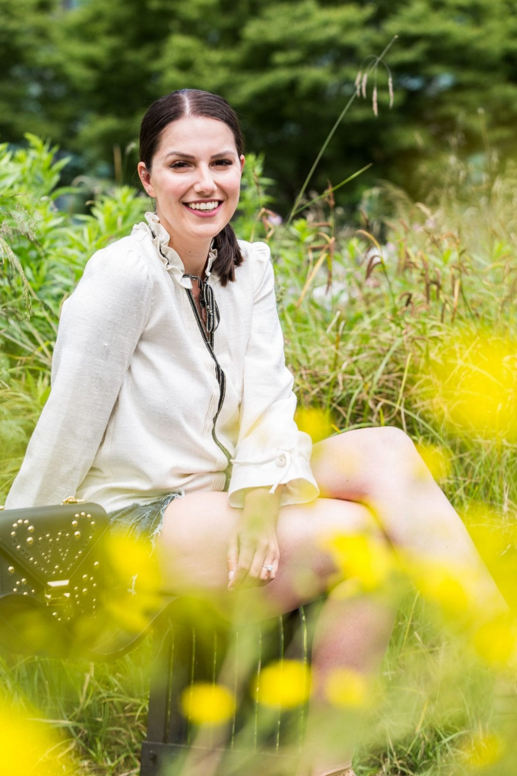 This is a close up of me smiling in a gorgeous white tunic top from Balzac Paris, while sitting in a park in Portland Oregon.