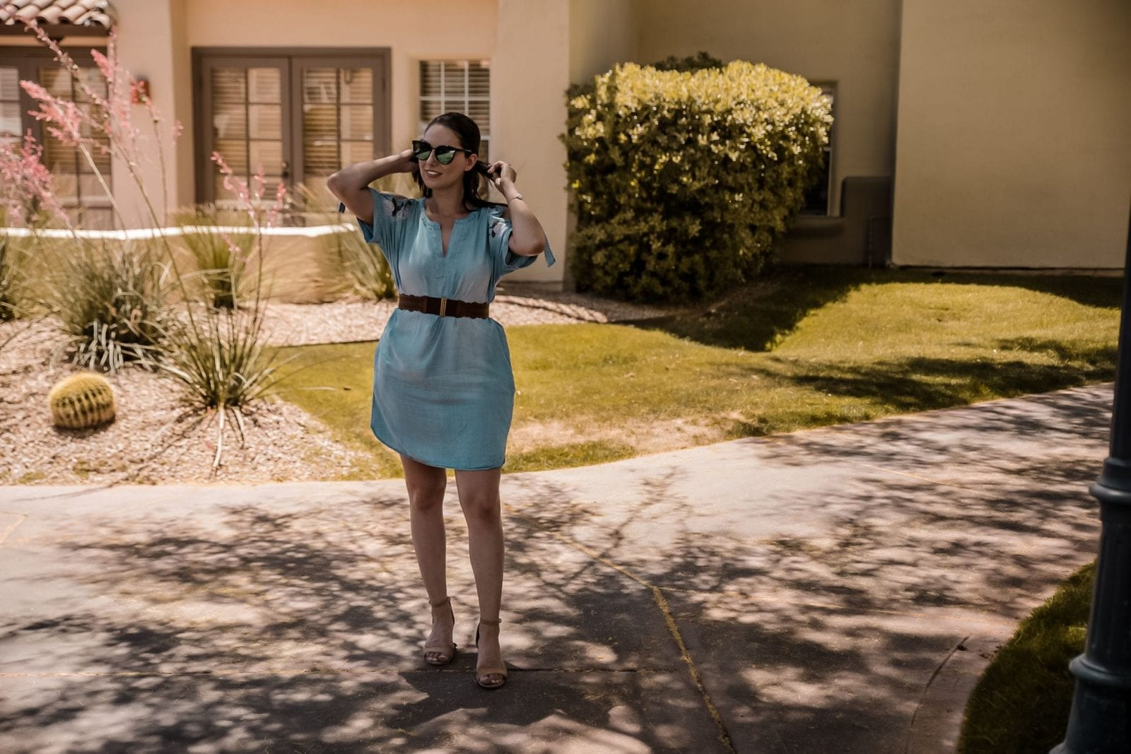 This is a portrait style shot of me fixing my ponytail outside in Scottsdale.