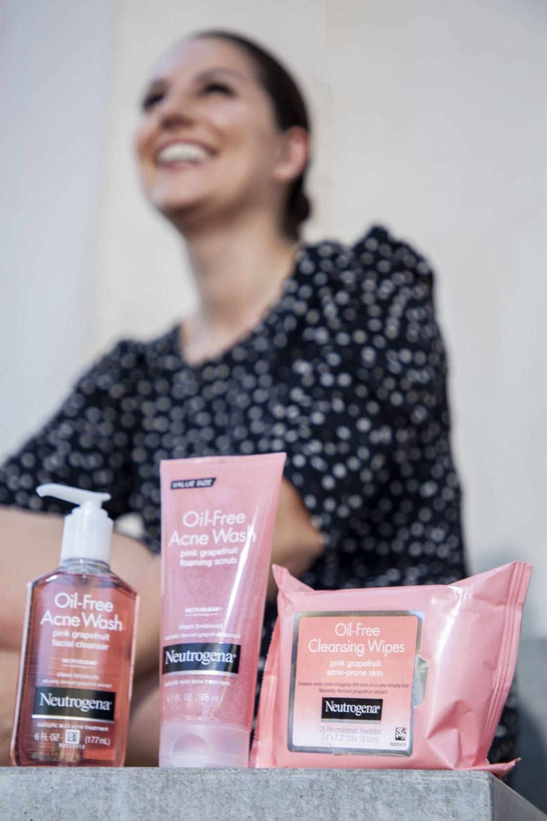 This is photo of me in a black polka dot dress with the Neutrogena Grapefruit Collection in front of me.