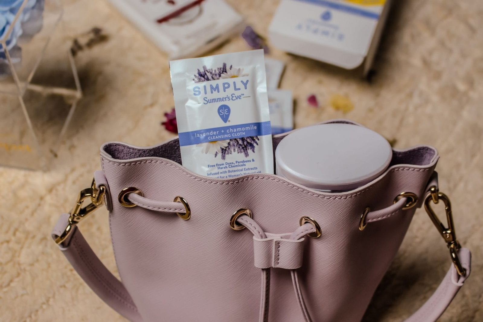 This is a close up shot of a lilac bucket bag, with Summer's Eve wipes sticking out.