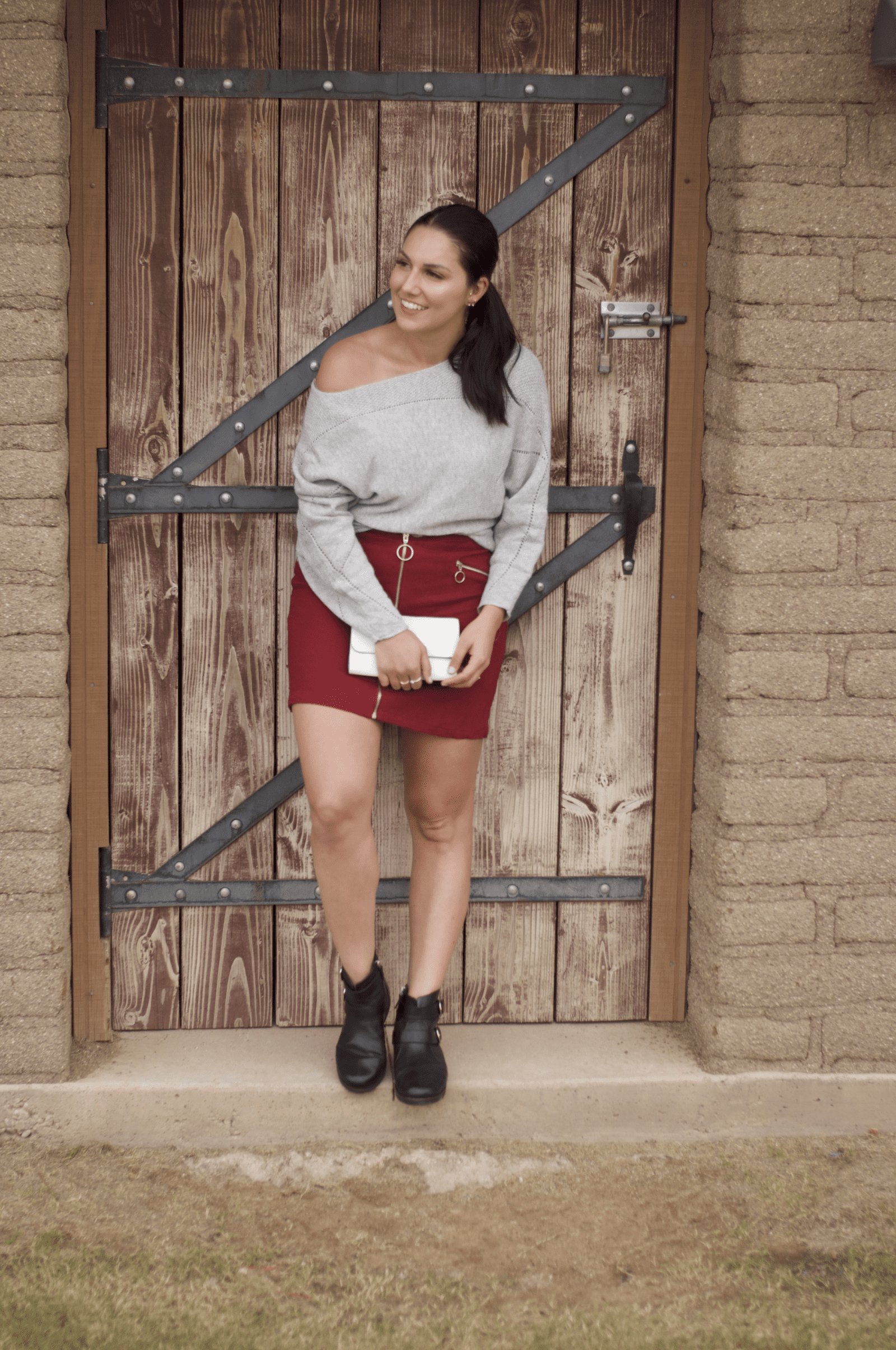 This is a full body shot of me rocking a maroon skirt and grey sweater with a black pair of booties from FitFlop.