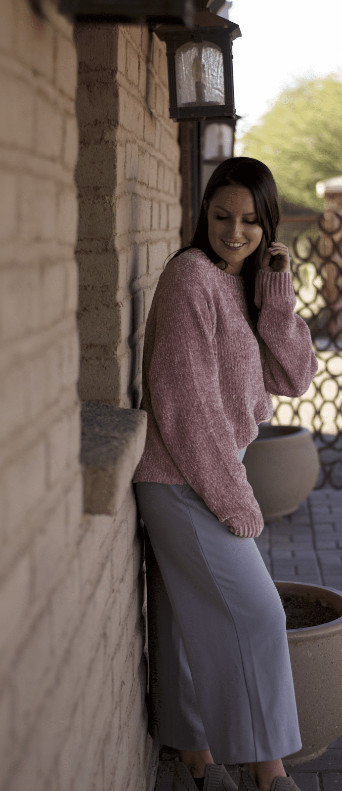 This is a full body shot of me in a pink sweater, with wide leg trouser pants standing against a wall.