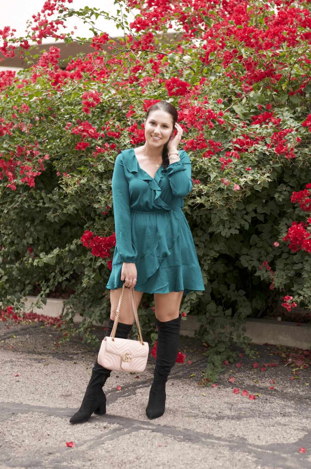 This is a full body shot of me in a teal dress from Express, with OTK boots and my pink Gucci bag.