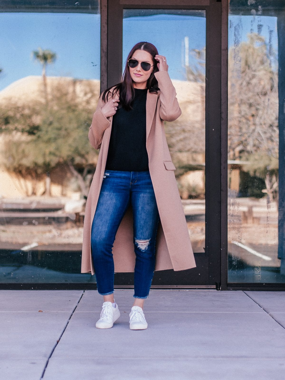 Adaleta Avdic is standing with a camel coat to her ankles, wearing a black sweater and dark blue denim with Josefinas embroidered sneakers.