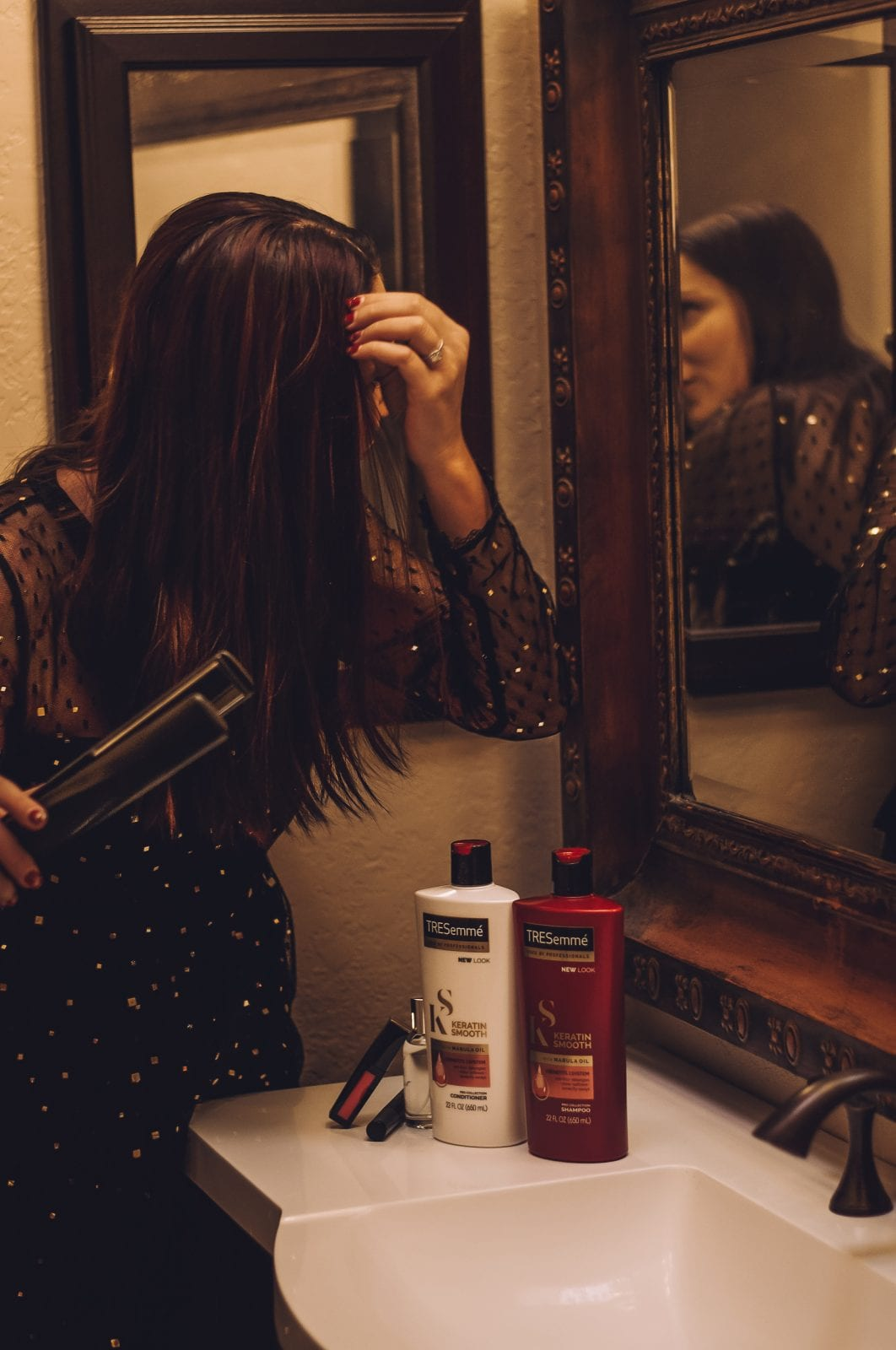 This is an in mirror shot of me straightening my hair in the mirror, while wearing a glitzy glam black dress for a night out.