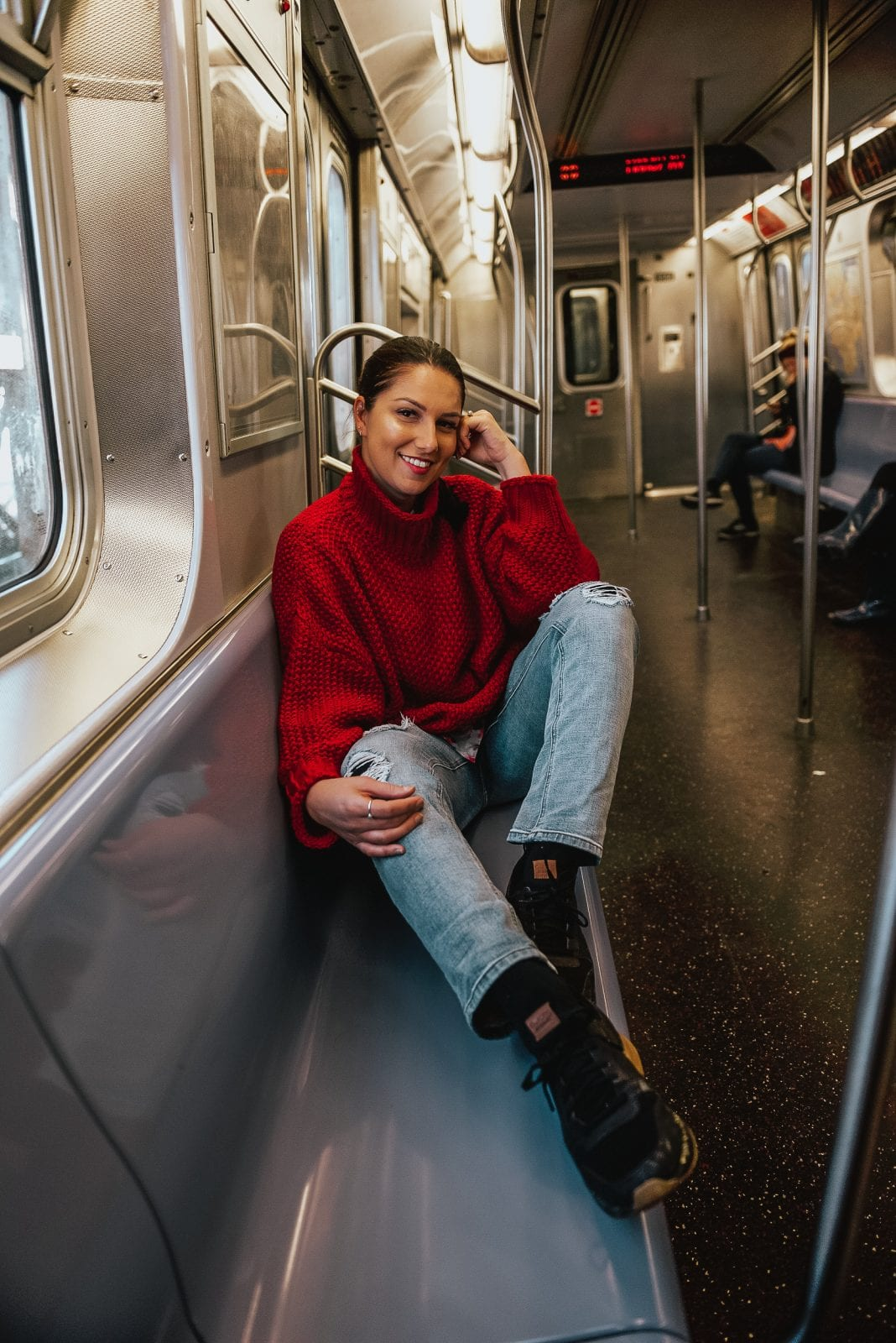 In this photo, I am sitting on the subway in New York heading to Brooklyn, in a red sweater, jeans and Dr Scholl's shoes.
