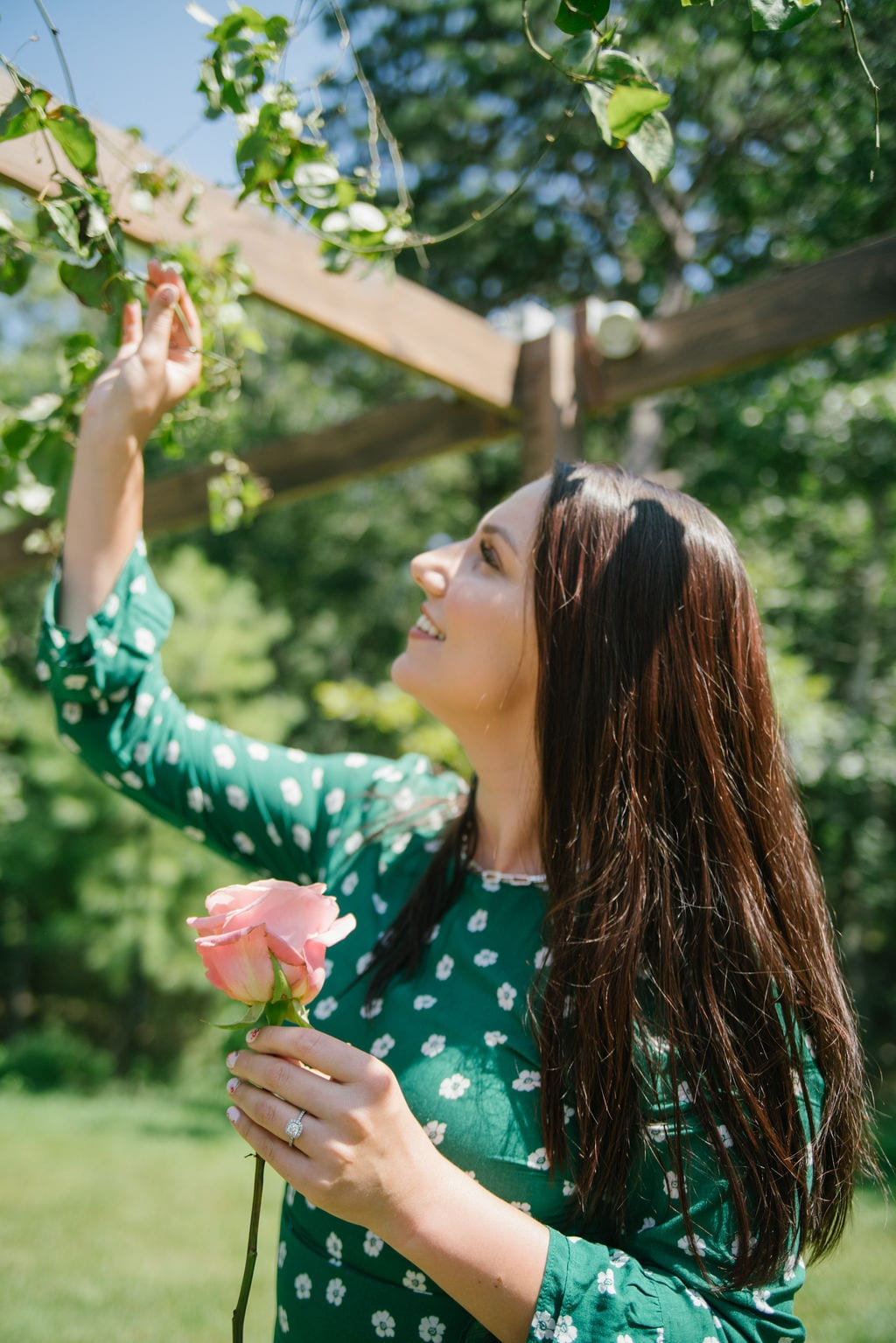 This is a photo of me wearing a green dress with white polka dots, while reaching for some roses in a bush up above, in Southhampton New York.