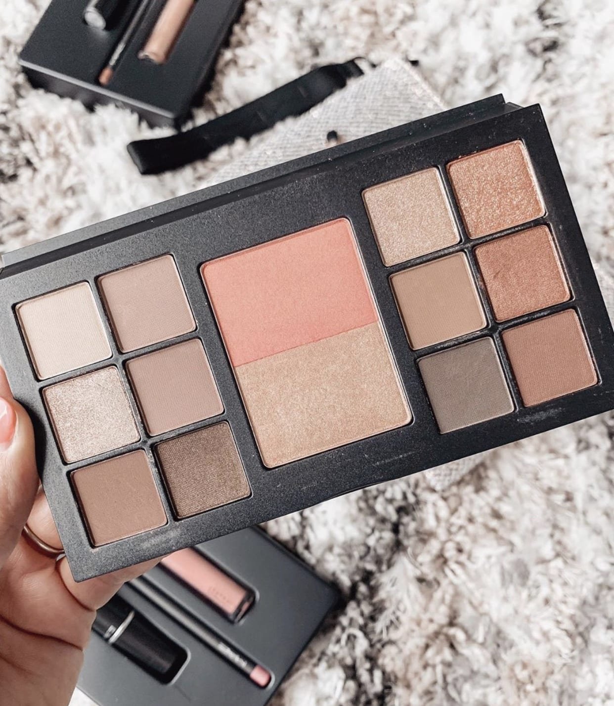 in this photo, Adaleta Avdic is showing her new palette from MAC that is filled with eyeshadows, bronzer, blush, and highlighter.