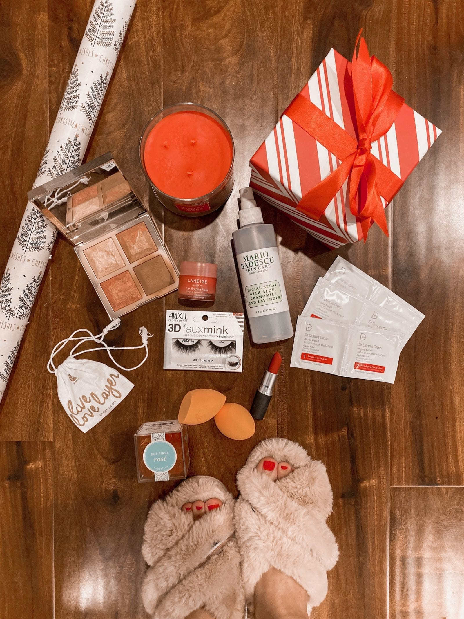 In this photo, Haley is sharing some of her favorite items that make great gifts for under $25. Next to the holiday wrapping paper, is sugarfina gummy bears, a beautiful contouring palette, a large, lavender setting spray, several bright orange beauty sponges. false lashes and our favorite peel pads from Dr. Dennis Gross.