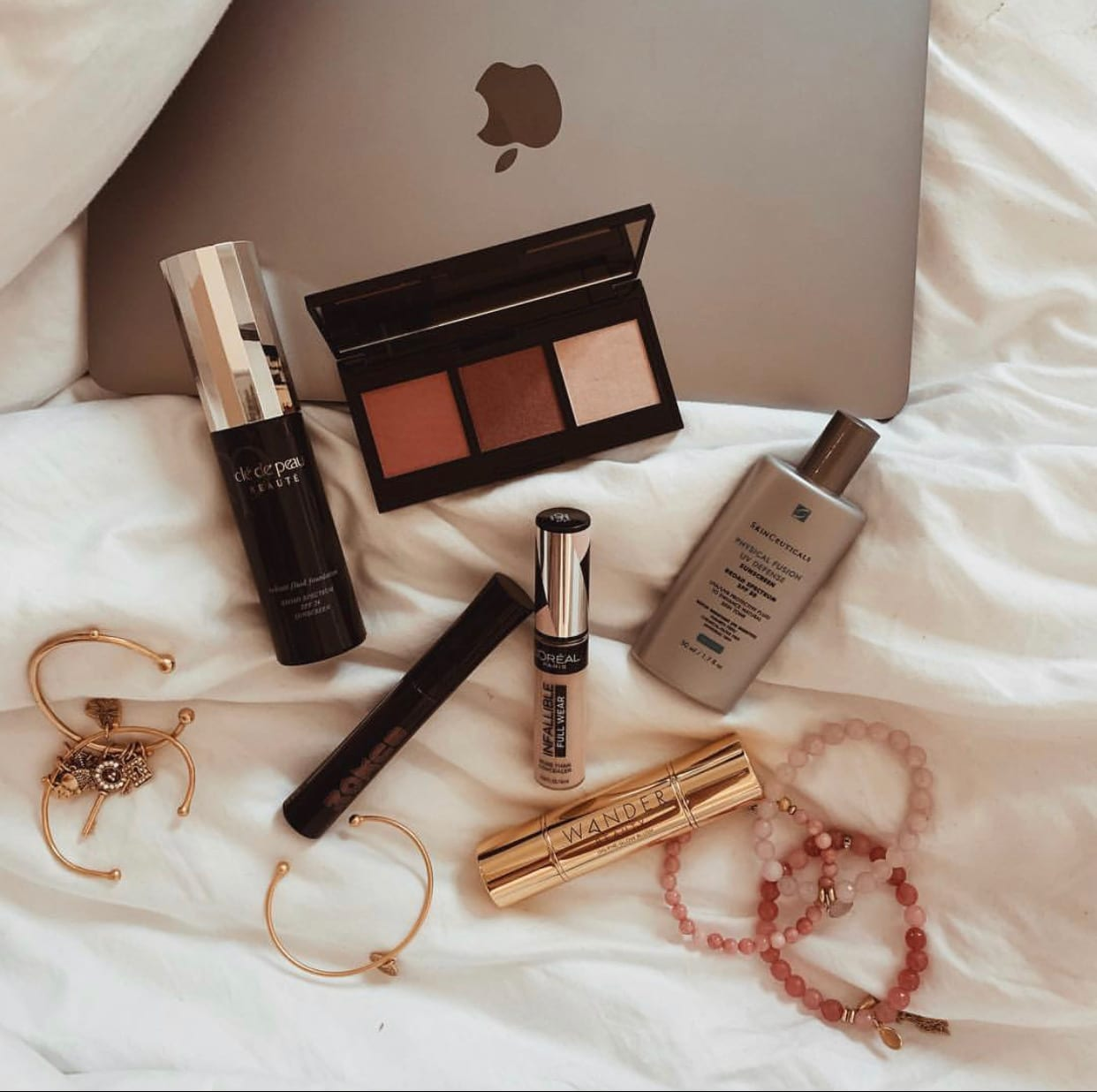 This is another flat lay featuring sunscreen, some makeup and jewelry.