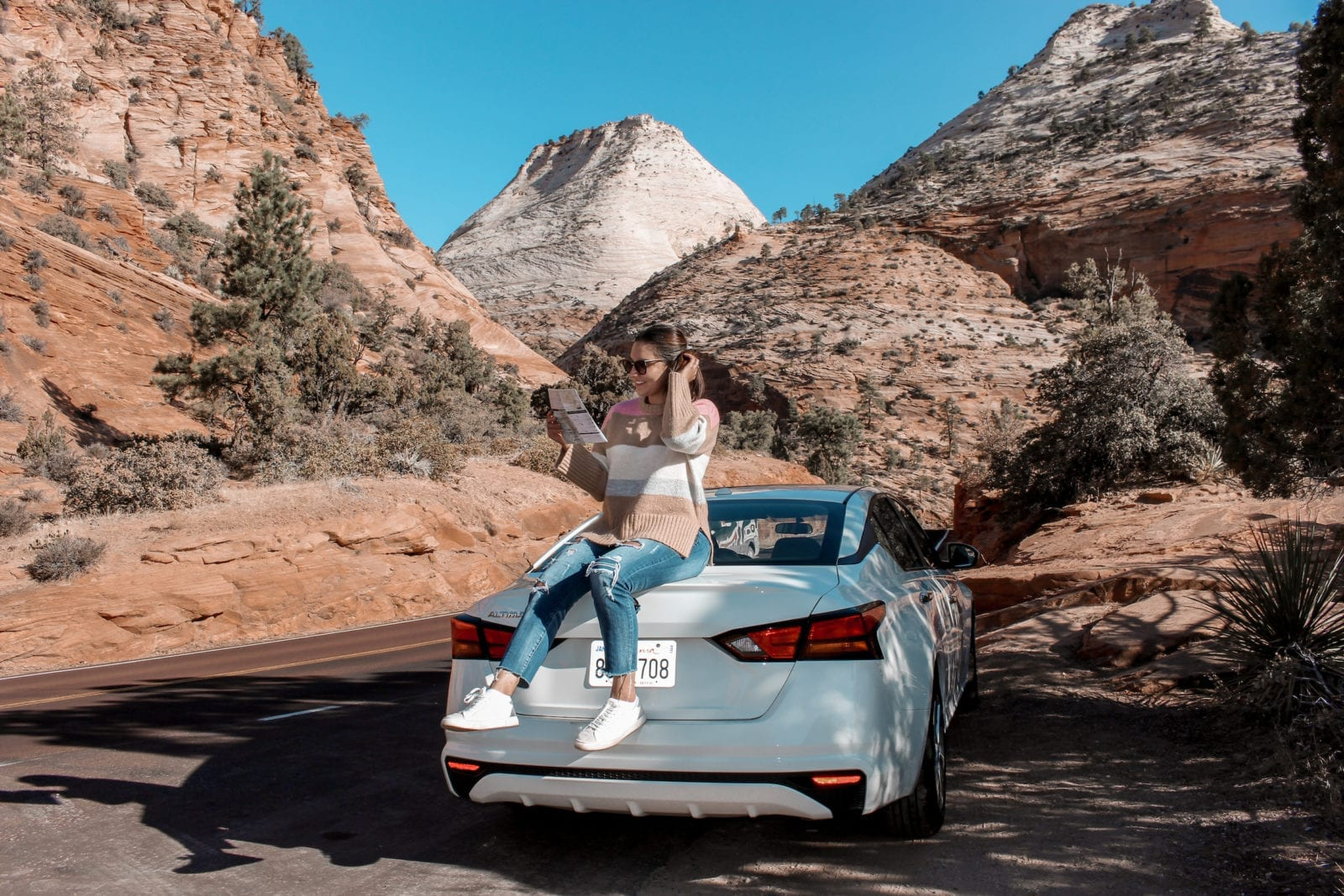 In this photo, Adaleta is sitting on top of white car in the middle of Zion National Park looking at a map of the park.