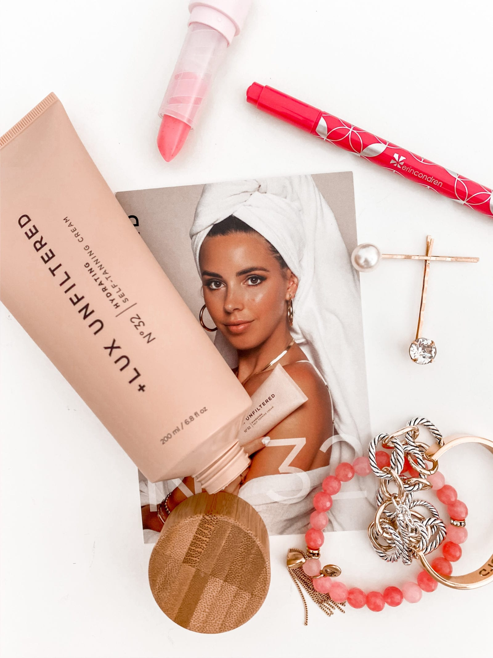 This is a flat lay photo including jewelry, some makeup items and the Lux Unfiltered Gradual Tan from Sivan Ayla.