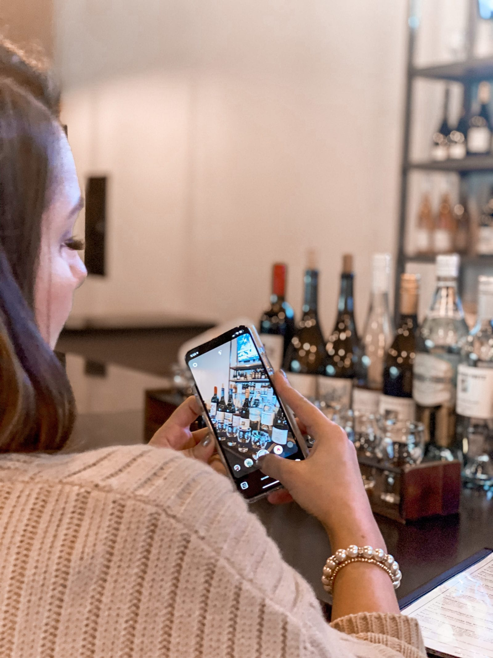 In this photo, Adaleta Avdic is taking a photo of the wine spread at Hop Street Lounge.