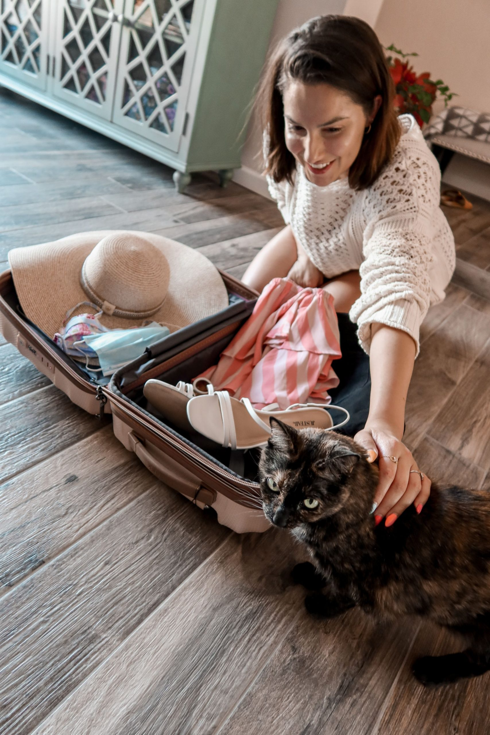 Adaleta Avdic is petting her tortoiseshell cat while packing for her trip post COVID lockdown.
