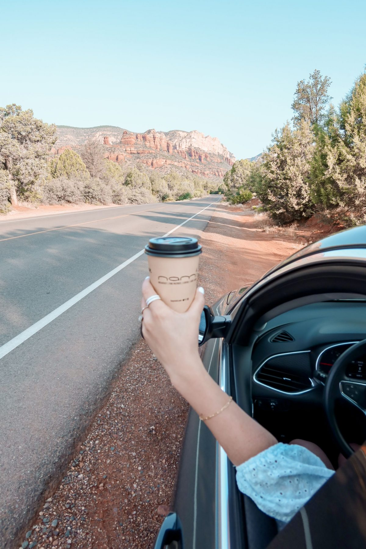 This is a photo of Ada holding her Nami's coffee, from Phoenix, outside the rental car with the Boynton Canyon mountains in the background in Sedona Arizona.