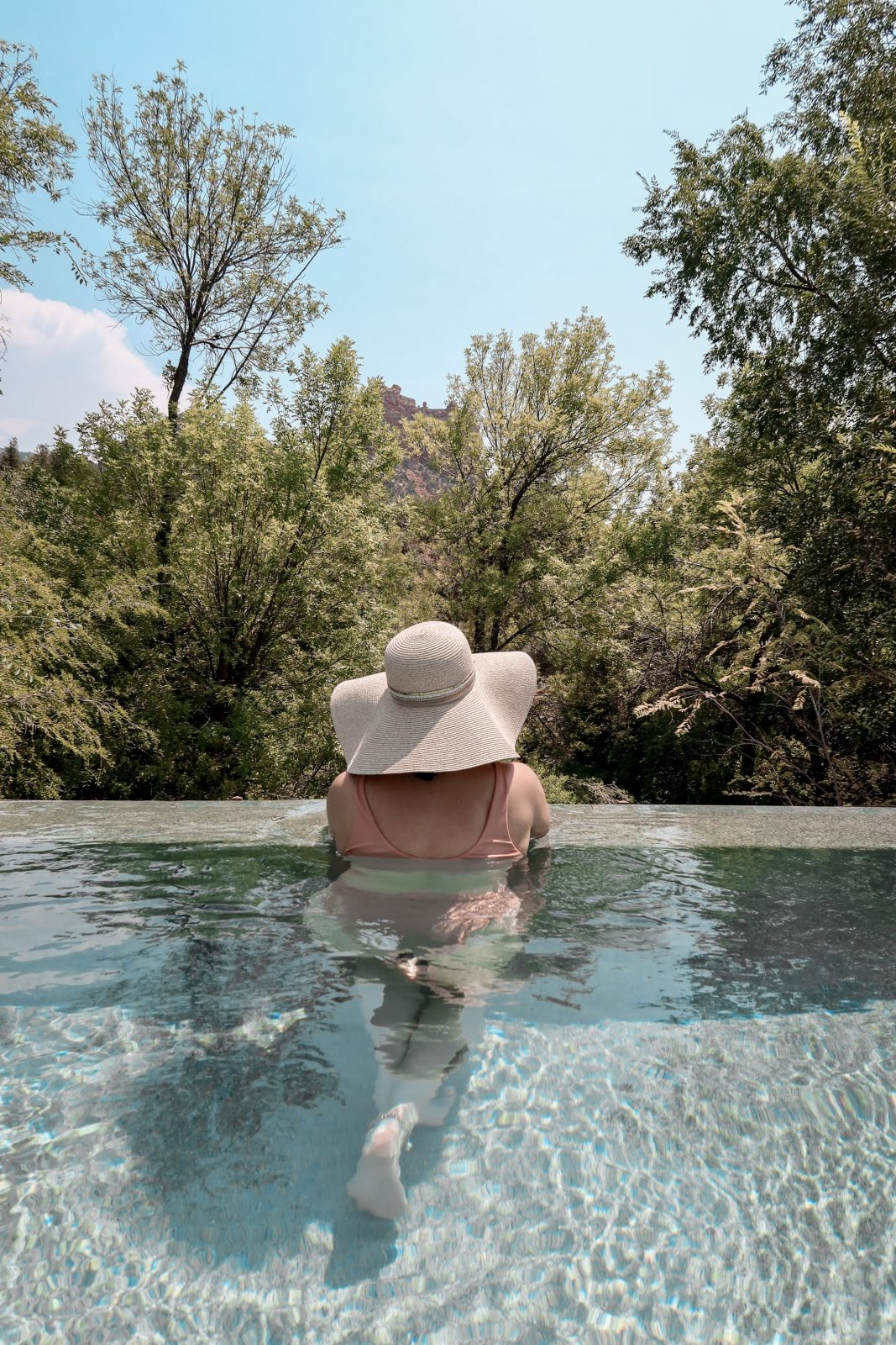 This is a photo of Adaleta Avdic in the Amara Resort & Spa pool, facing the mountains of Sedona in the background.