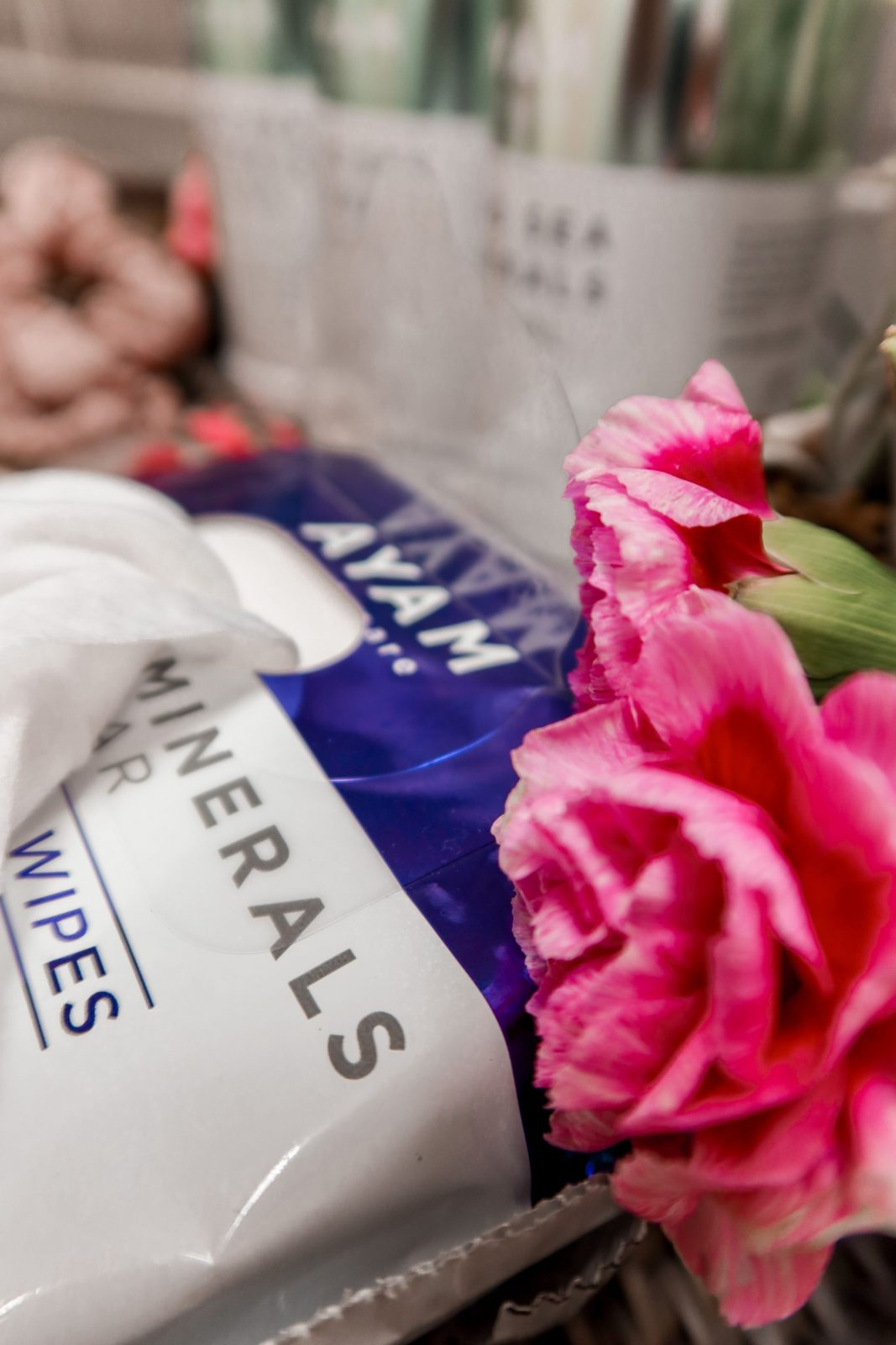 This is a close up of the Ayam Beauty makeup removing wipes, with some beautiful pink flowers as a prop to the side.