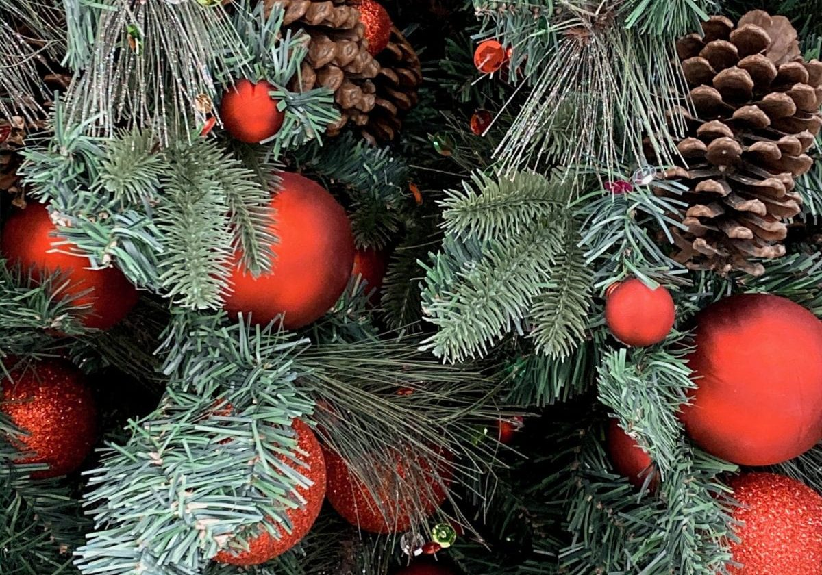 In this photo, beautiful pine garland is draped alongside red and green sequins, pine cones and red bulb ornaments.