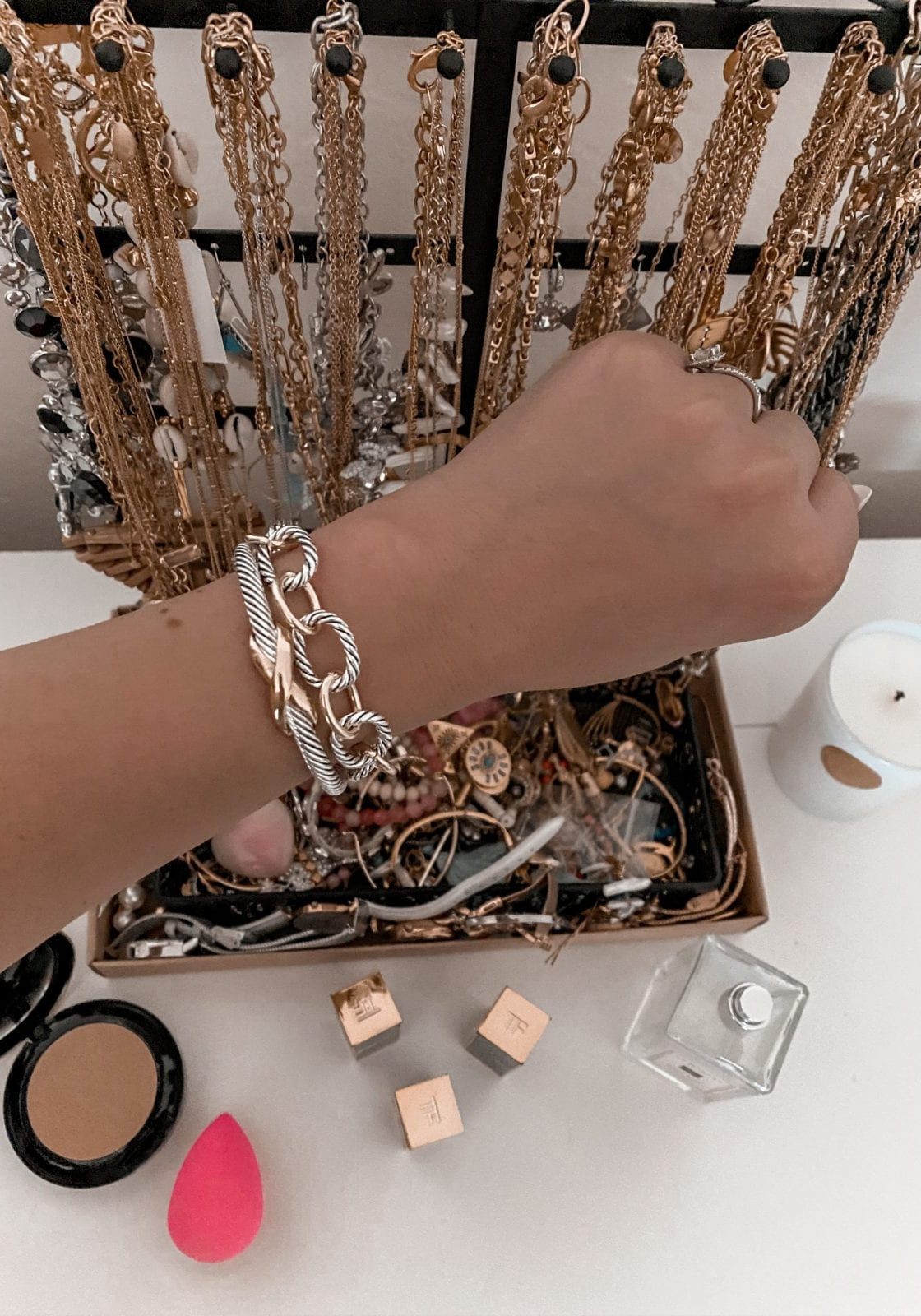 In this image, Adaleta is showing off some of her Amazon Prime designer dupes. She's rocking two of the David Yurman Dupes available on prime for less than $20. She's holding her arm out in front of her jewelry tree on her desk in her beauty room.
